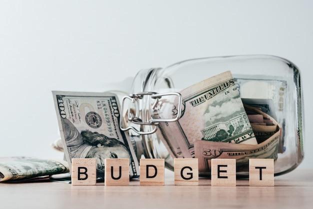 Word budget and dollar bills in glass jar Premium Photo