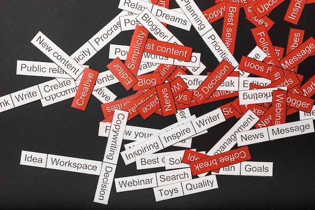 Word cloud of business themes cut out of red and white paper on a gray background Premium Photo