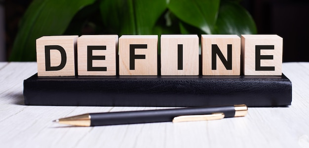 The word define is written on the wooden cubes that lie on the diary near the pen. Premium Photo