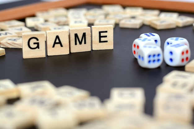 Word game with wooden letters on black board with dice and letter in the circle, Premium Photo
