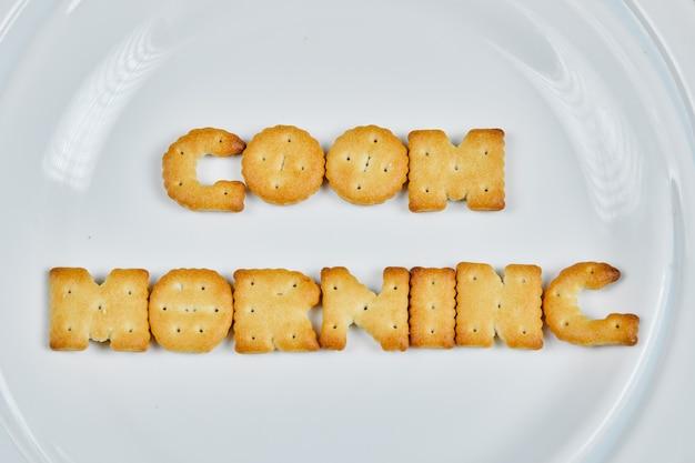 Слово доброе утро пишется с крекерами на белой тарелке. Бесплатные Фотографии