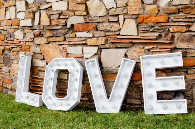 A word of love near the stone wall. photo area in wedding decoration in the park Premium Photo