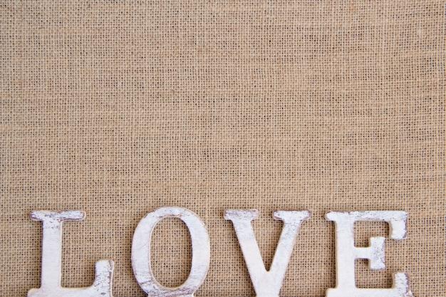 Слово любовь на вид сверху мешковины с копией пространства Premium Фотографии