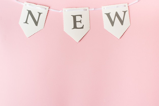 Word new on pastel pink background, top view with copy space Premium Photo