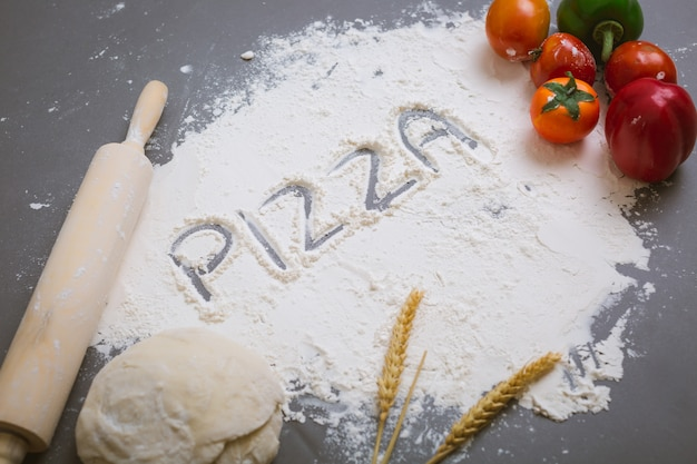 Word pizza written on flour with ingredients Free Photo