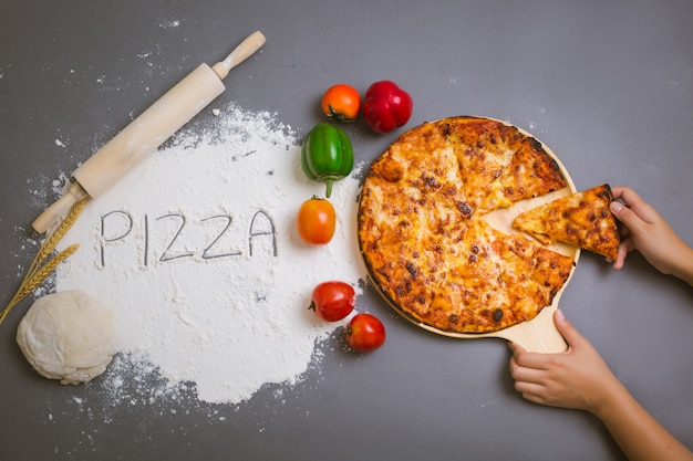 Word pizza written on flour with a tasty pizza Free Photo
