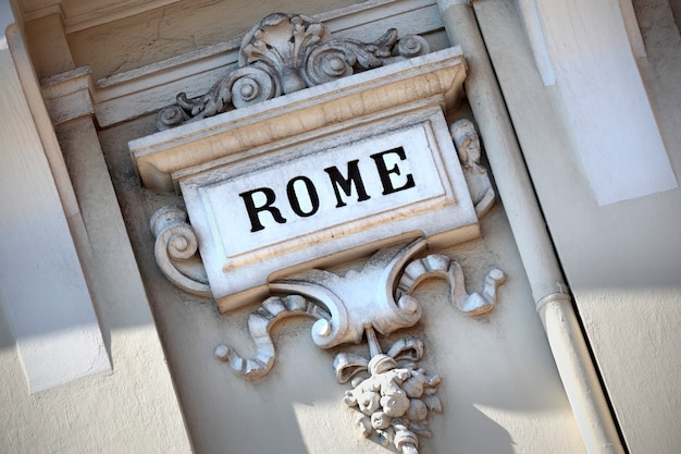 The word rome carved in an old sculpted wall. Free Photo