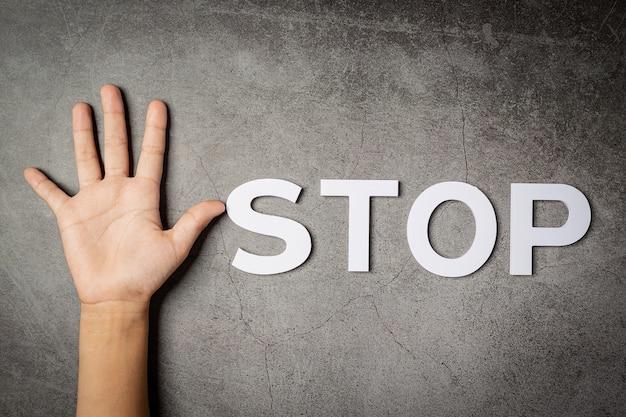 暗い壁に子供の手で「停止」という言葉 無料写真