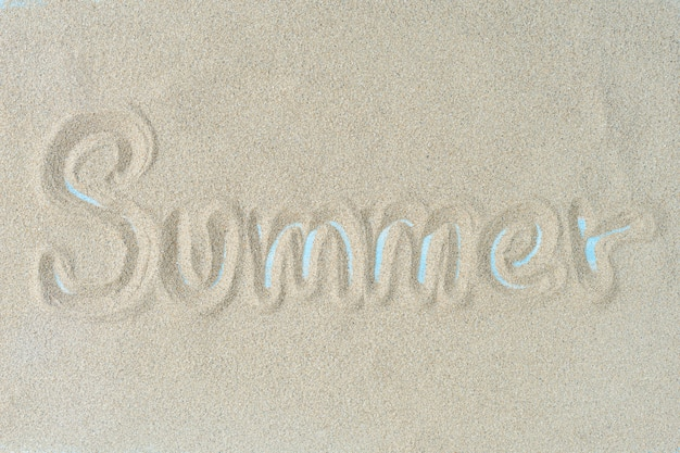 The word summer is writting on the sand. summer background. Premium Photo