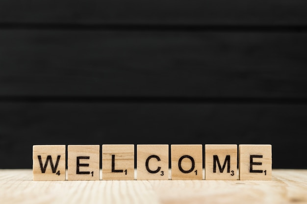 The word welcome spelt with wooden letters Free Photo