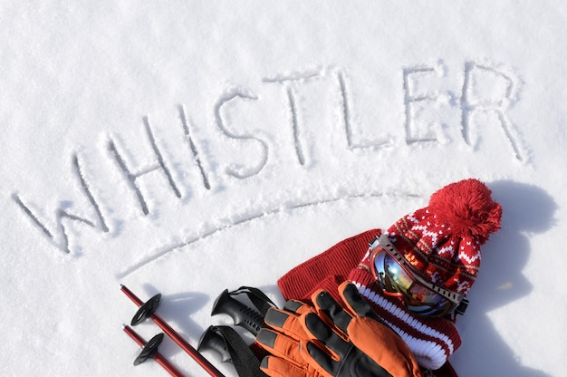 The word whistler written in snow with ski poles, goggles and hats Free Photo