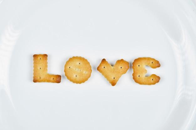 Вкусное слово пишется с крекерами на белой тарелке. Бесплатные Фотографии