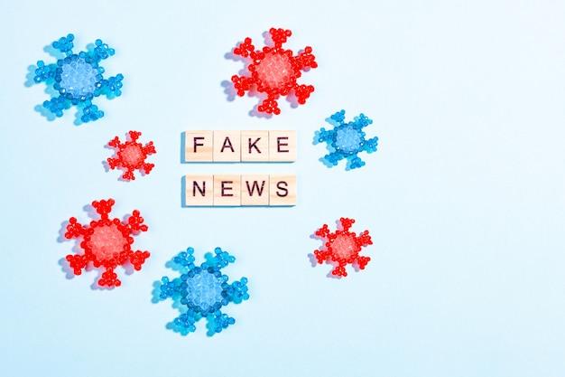青色の背景にコロナウイルスモデルと木製のブロックで作られた偽の言葉の言葉 Premium写真