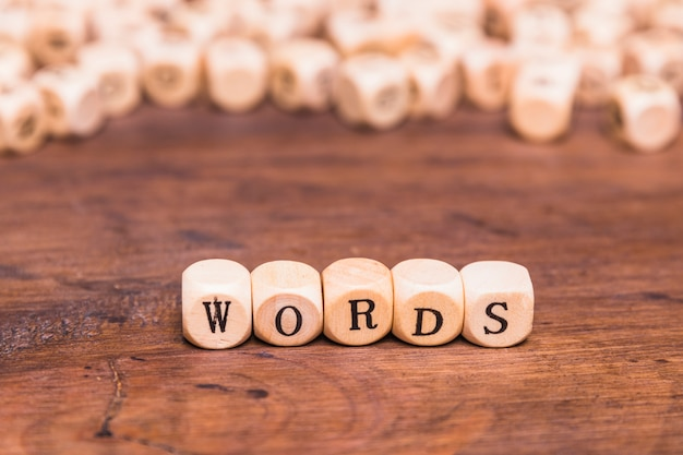 Words letter made with wooden cubes over brown desk Free Photo
