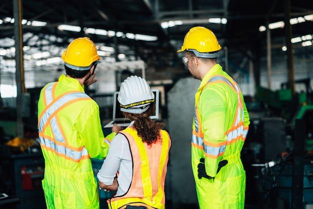 공장에서 일하십시오. 노동자 남자와 엔지니어 여자 팀은 공장 작업장 산업 개념 전문 노트북 Computer.in를 사용하여 흰색과 노란색 헬멧을 사용하여 안전 작업 착용에 협력 프리미엄 사진