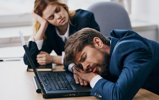 직장 동료는 노트북 피로 휴식 앞에 책상에서 자고 프리미엄 사진