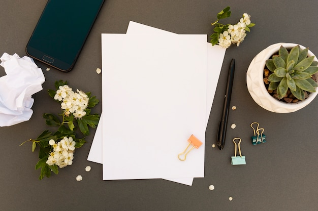 Work desk, table mock up with smartphone, blank pappers, spring flowers frame. office work table. copy space. Premium Photo