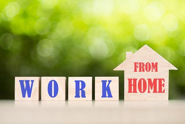 Работа из дома текст с деревянным игрушечным домиком Premium Фотографии