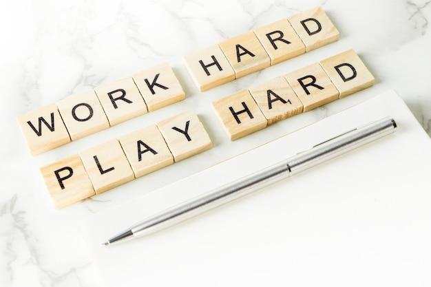 Work hard play hard text on scrabble wood in office desk concept Premium Photo