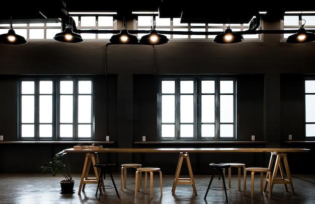 Рабочий стол в темном лофт-кафе с большим окном Premium Фотографии
