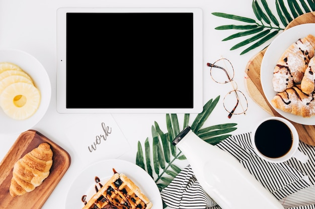 Work text on paper near the digital tablet; pineapple slices; croissant; waffles; bottle; coffee cup and eyeglasses on white desk Free Photo