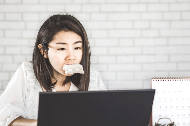 Workaholic and busy asian woman no time to eat Premium Photo