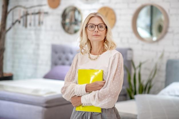 ワークブック。家具店のサロンに立っているノートの黄色いノートをつかんで深刻なビジネス女性。 Premium写真