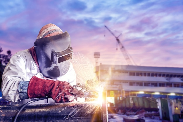 Worker arc welder piping welding buiding in shipyard background soft monoto Premium Photo