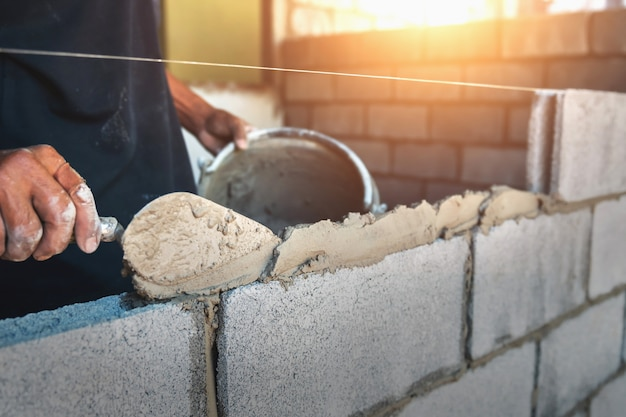 Worker building wall bricks with cement Premium Photo