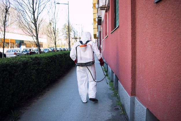 Lavoratore in tuta di protezione chimica che spruzza disinfettante su superfici pubbliche Foto Gratuite