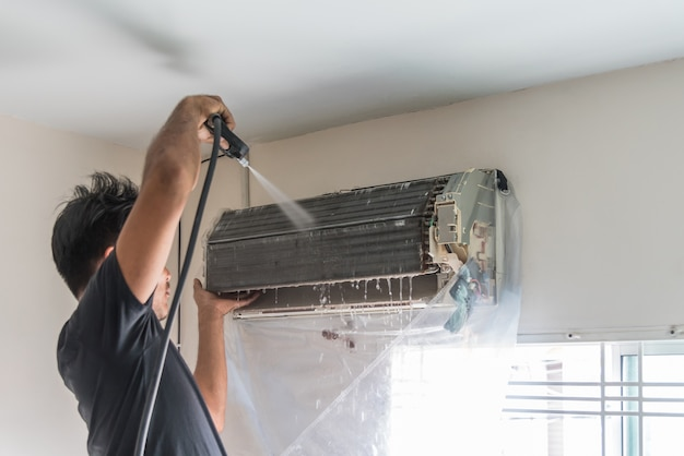 Worker to cleaning coil cooler of air conditioner Premium Photo