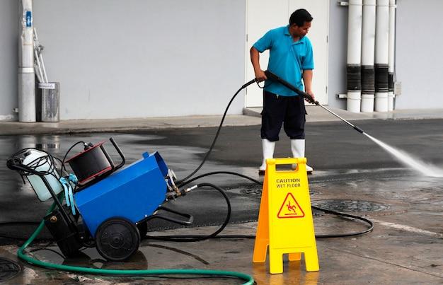 Worker cleaning floor with air high pressure machine - Toolbox Talks on Housekeeping