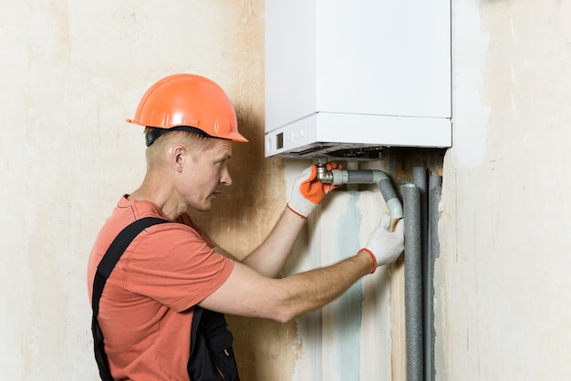 Worker connecting the pipes to a domestic gas boiler Premium Photo