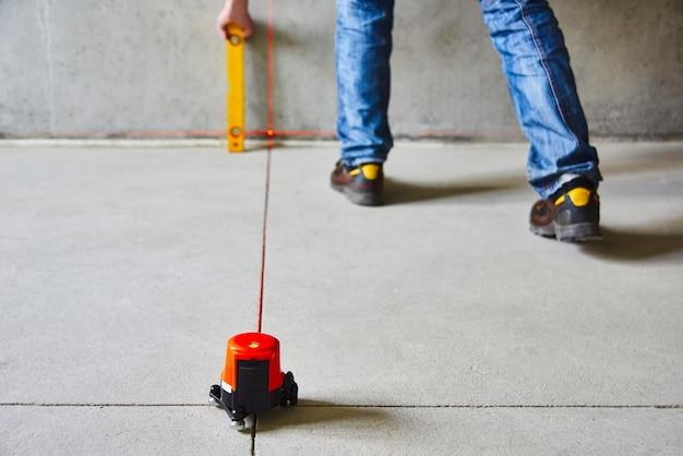 Рабочий контролирует работы стен с помощью лазерного уровня линии. лазерное рулеточное устройство Premium Фотографии