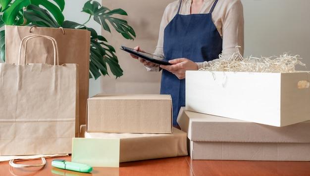 Работник службы доставки упаковочная сумка коробка фартук упаковщик ручное почтовое отделение Premium Фотографии