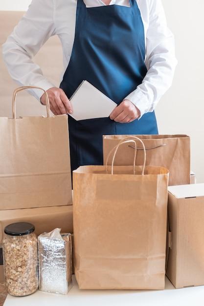 Служба доставки работника упаковочная сумка коробка фартук упаковщик рука почтовая накладная Premium Фотографии