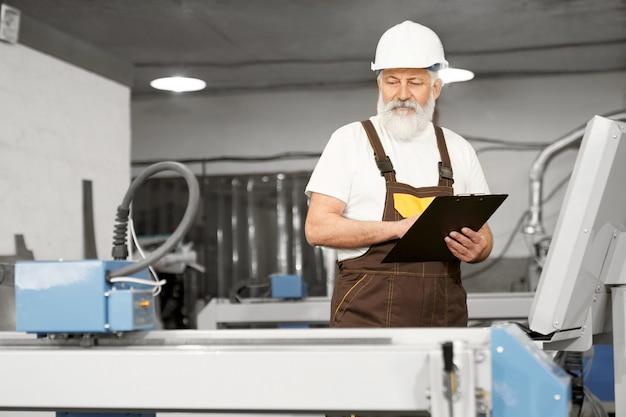 Lavoratore della cartella di detenzione di fabbrica, osservando la taglierina laser. Foto Gratuite