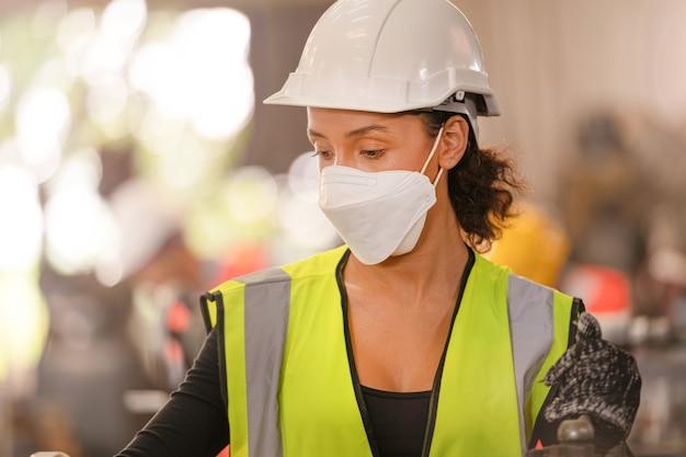 작업자 공장 사람들이 얼굴 마스크와 안전 복을 입고. 공장에서 일하는 여성. 프리미엄 사진