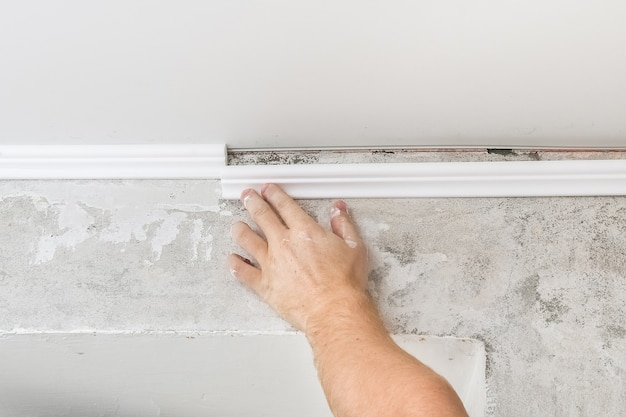 Worker fixes the plastic molding to the ceiling. installation of ceiling cornice. Premium Photo