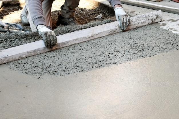 コンクリートの床を平らにする労働者 Premium写真