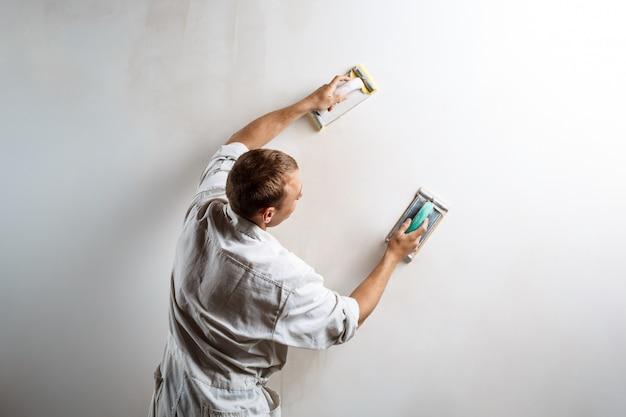 Lavoratore che macina parete bianca con carta vetrata. Foto Gratuite