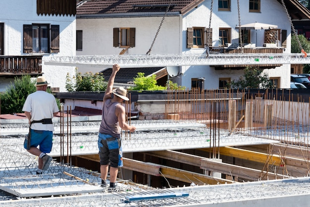 Worker guides the descending concrete slab at the