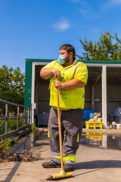 Работник фабрики по переработке отходов или чистой точки и мусора в маске и с защитными приспособлениями. портрет рабочего с метлой Premium Фотографии