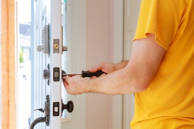 Worker installing or repairing new lock Premium Photo