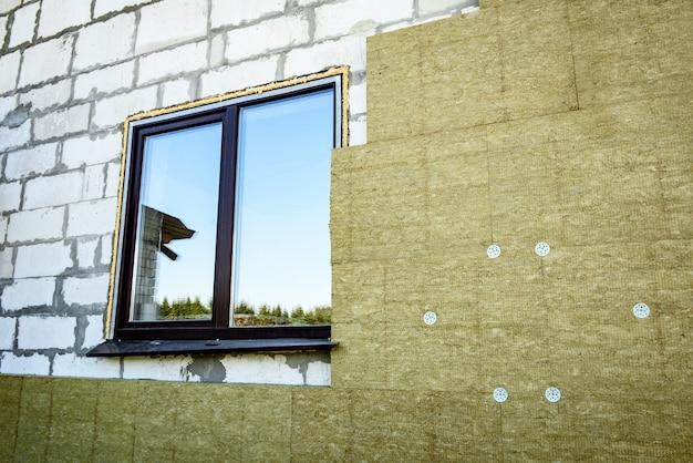 Рабочий утепляет дом плитами из минеральной ваты. внутренняя теплоизоляция стен минеральной ватой. Premium Фотографии