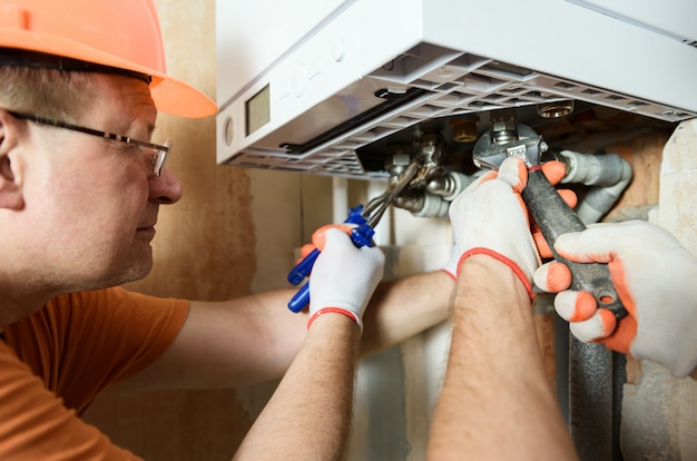 The worker is installing the gas boiler pipes. Premium Photo
