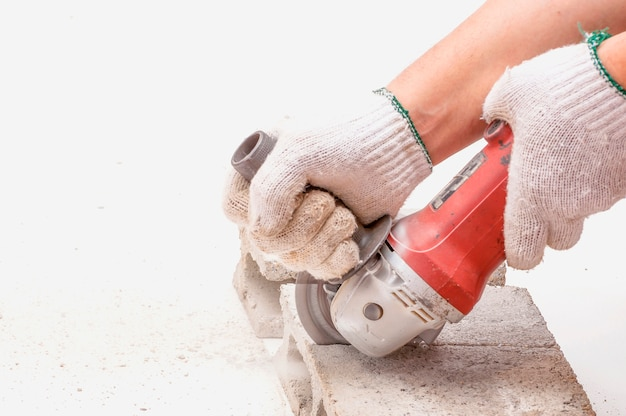 Worker is using angle grinder for cutting cement block, hand tool, focus at blade Free Photo