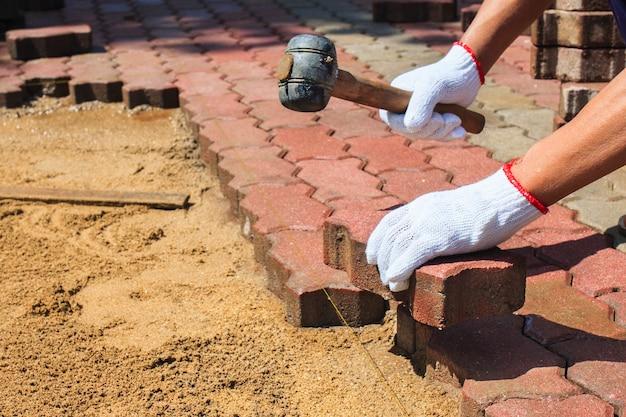 Worker laying red concrete paving blocks. Premium Photo
