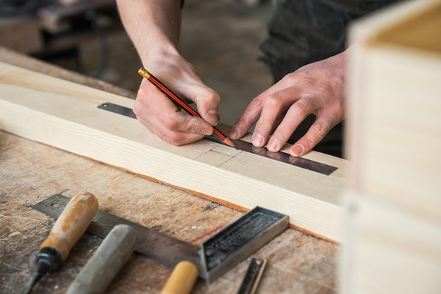 The worker makes measurements of a wooden board Premium Photo