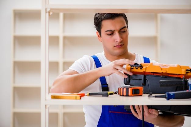 Worker man repairing assembling bookshelf Premium Photo
